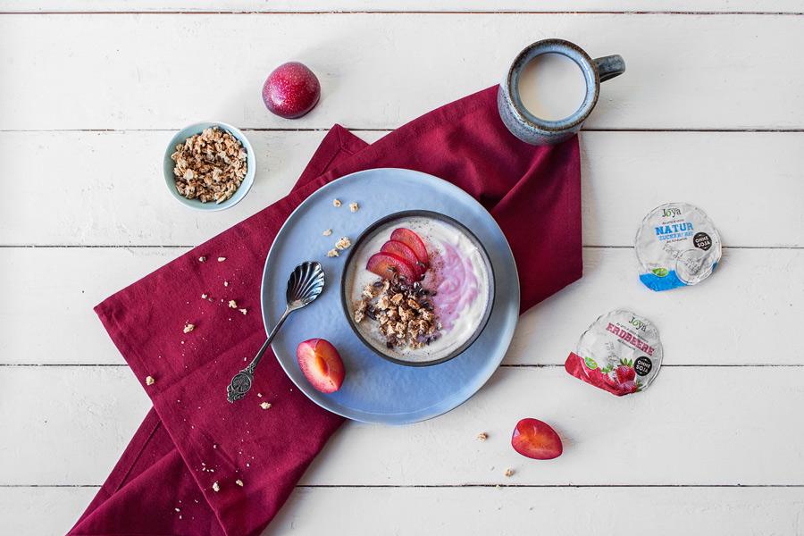 Die Sorten Natur und Erdbeere vom Joya-Kokosjoghurt serviert